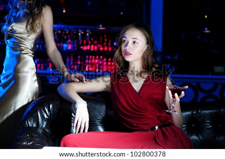 young woman has a rest with an alcoholic drink, second woman on a background - stock photo