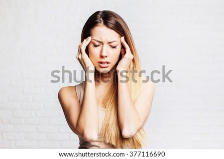 Young woman has headache, on a gray background - stock photo