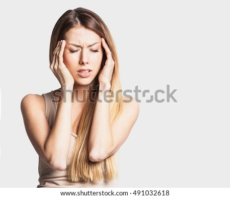 Young woman has headache, on a gray background