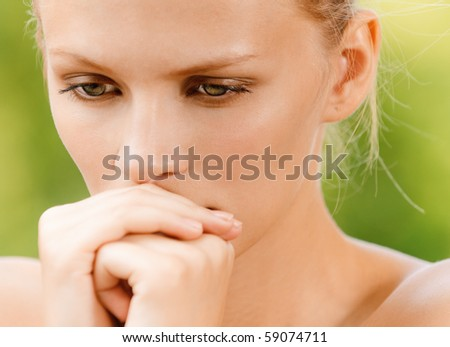 Young woman has inclined head and reflects. - stock photo