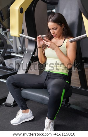 Young woman having a break in a health club and text messaging on cell phone.