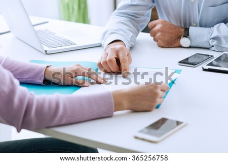 Young woman having a business meeting with an executive in his office, he is pointing on a contract and giving explanations - stock photo