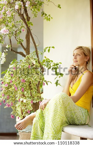 Young woman having a conversation on a cell phone in a home garden. - stock photo