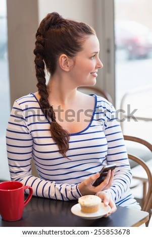 Young woman having a cupcake at the cafe - stock photo