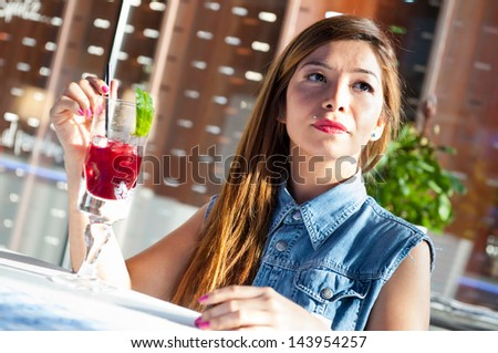 Young woman having a drink in a bar.