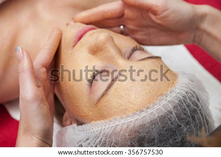 Young woman having a face massage and a peeling treatment at a beauty salon.