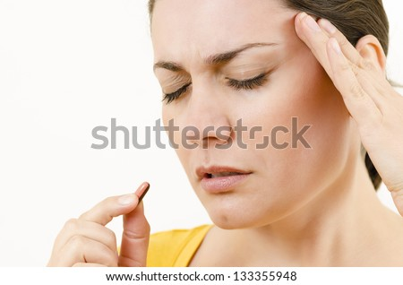 Young woman having a headache holding a pill - stock photo