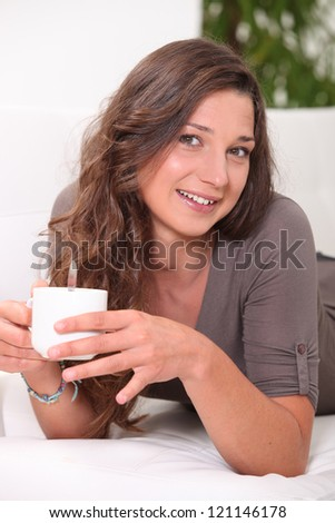 Young woman having a hot drink at home - stock photo