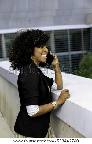 Young woman having a pleasant conversation using her cell phone while on a balcony.