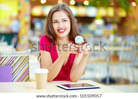 Young woman having a rest after shopping at the ice cream bar