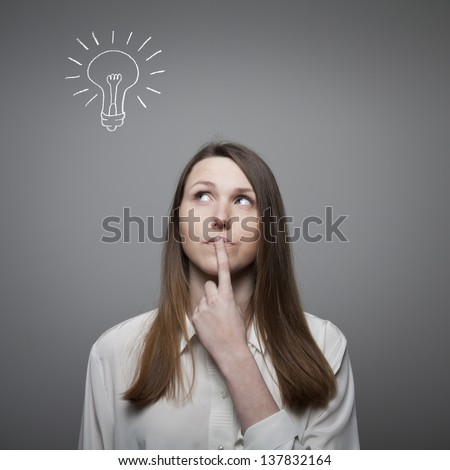 Young woman having an idea with light bulb over her head - stock photo