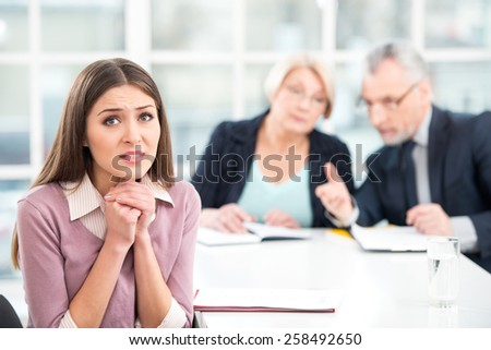 Young woman having an interview or business meeting with employers. Woman really wanting to get the job. Office interior with big window - stock photo
