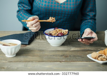 young woman having breakfast and checking her mobile phone on wooden table - stock photo