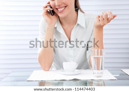 Young woman having breakfast using cellphone.