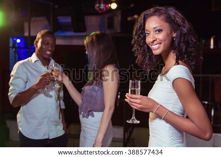 Young woman having champagne in bar while her friends having fun in background - stock photo