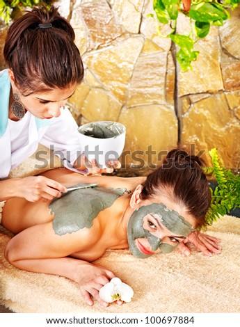 Young woman  having clay facial mask. - stock photo