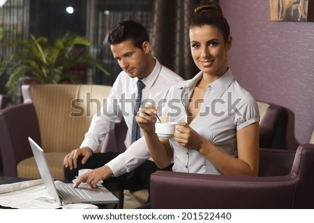 Young woman having coffee at hotel lobby, working late with colleague on business trip. - stock photo