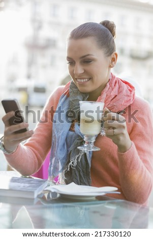 Young woman having coffee while using cell phone at sidewalk cafe - stock photo