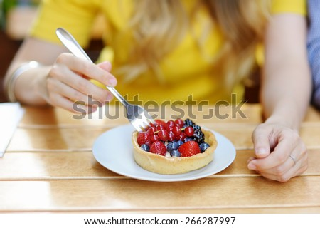 Young woman having custard fruit tart in the outdoors cafe