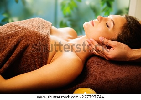 Young woman having face massage in a spa salon - stock photo