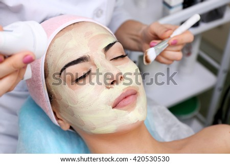 Young woman having face procedures in a beauty salon - stock photo