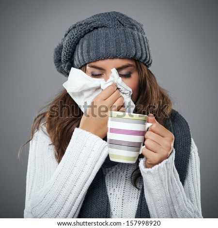 Young woman having flu and blowing her nose at handkerchief - stock photo