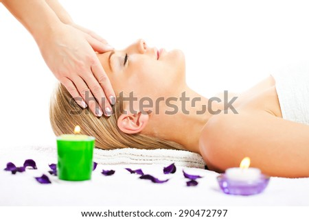 Young woman having forehead massage on spa treatment