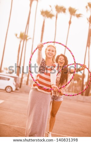 Young Woman having fun at the beach with Hula Hoops in Venice Beach California - stock photo