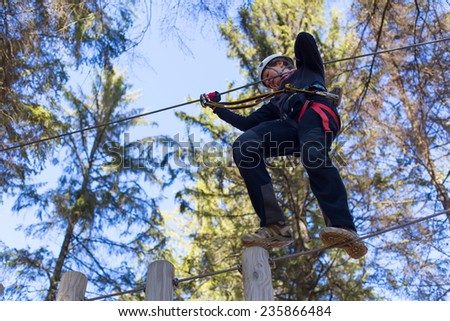young woman having fun in an outdoor adventure park - stock photo