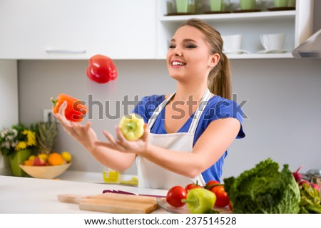 Young woman having fun in kitchen, juggle with vegetables - stock photo
