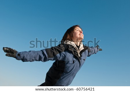 Young woman having fun on blue sky in winter time - joy and happines emotions