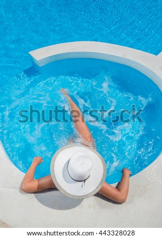 Young woman having good time in swimming pool - stock photo