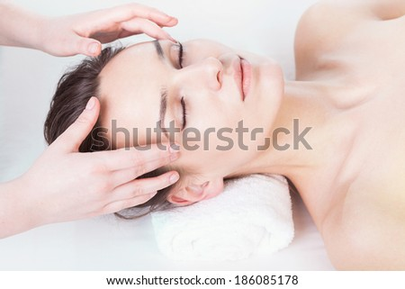Young woman having head massage at spa salon - stock photo