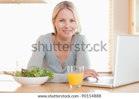 Young woman having healthy lunch while working on her notebook - stock photo