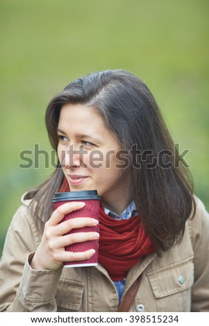young woman having her coffee with blurred meadow as background - stock photo