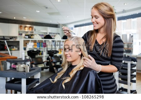 Young woman having her hair dyed by beautician at parlor - stock photo