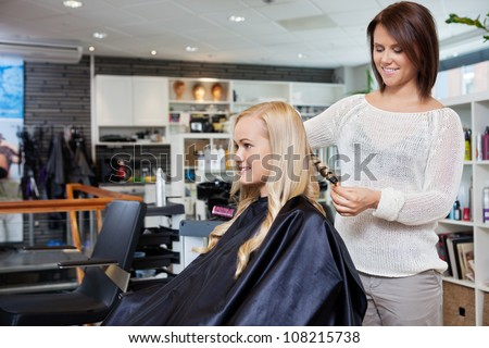 Young woman having her hair styled by beautician at parlor - stock photo