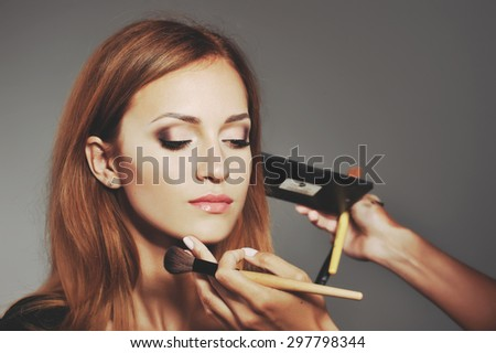 Young woman having make up applying by artist in studio.  - stock photo