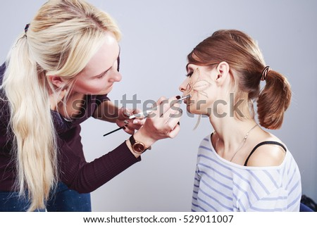young woman having make up applying by artist in studio