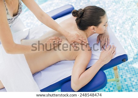Young woman having massage at the pool - stock photo