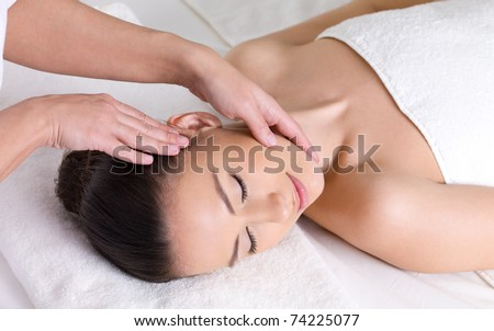 Young woman having massage for the skin of her beautiful face