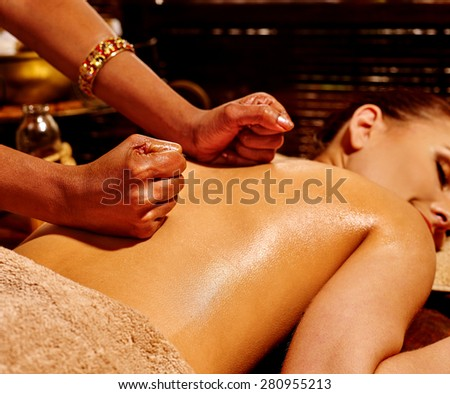 Young woman having oil Ayurveda spa treatment. Indian hands.