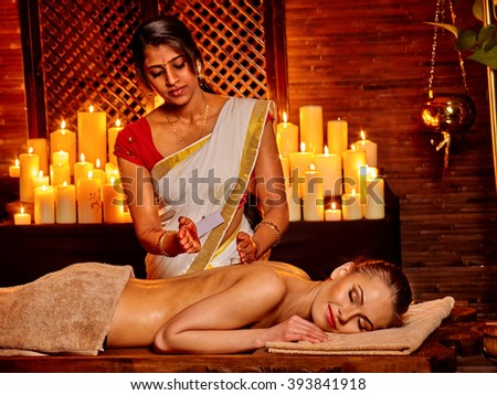 Young woman having oil Ayurveda spa with burning candels.  - stock photo