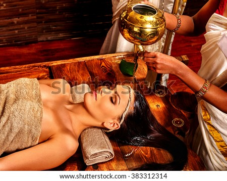 Young woman having oil head Ayurveda spa treatment. - stock photo