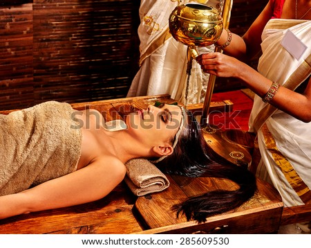 Young woman having pouring oil Ayurveda spa treatment. - stock photo