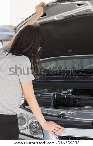Young woman having problems standing checking breakdown car in front of her car because her car engine failed