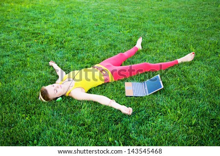 Young woman having rest in the park with laptop - stock photo