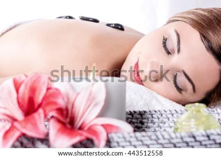Young woman having stone massage in spa salon - stock photo