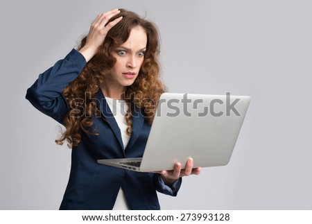 Young woman having trouble with laptop. Studio shot - stock photo
