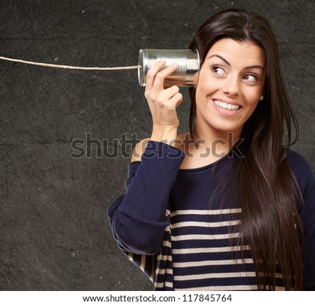 Young woman hearing using a metal tin can against a grunge wall - stock photo